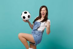 Extatiskt fotbollsfanjubel för ung kvinna upp det favorit- laget för service med fotbollbollen som griper hårt om näven som den i royaltyfria foton