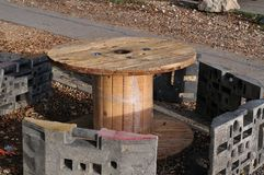 Extemporaneous resting place beside construction site. Resting place beside construction site, improvised with empty wooden cable spool and kiln furniture of stock photos