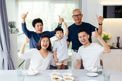 Extended Asian family of three generations having a meal together and showing thumbs up at home with happiness stock photo
