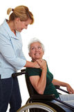 Extended care nurse helping senior. Extended care nurse helping disabled senior women in wheelchair royalty free stock image
