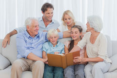 Extended cheerful family looking at a photo album Royalty Free Stock Image