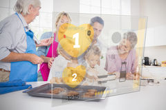 Extended family baking together with futuristic interface Stock Photo