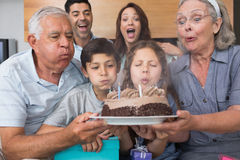 Extended family blowing candles on cake in living room Royalty Free Stock Image