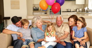 Extended family celebrating little girls birthday on couch stock footage