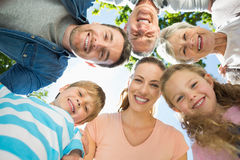 Extended family forming huddle in park Stock Photo