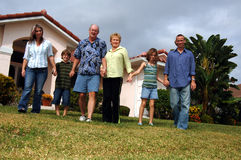 Extended family in front of home. A happy extended family of parents with two children and grandparents holding hands in front of house stock images