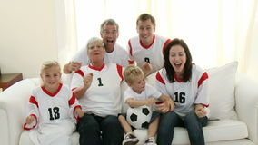 Extended Family with grandparents on the sofa watching Football. Filmed on 1080p stock video footage