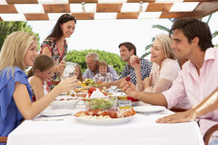 Extended Family Group Enjoying Outdoor Meal Together Stock Photography