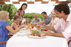 Extended Family Group Enjoying Outdoor Meal Together Royalty Free Stock Images
