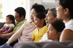 Extended Family Group At Home Watching TV Together Stock Images