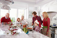 Extended Family Group Preparing Christmas Meal In Kitchen Stock Photos