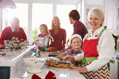 Extended Family Group Preparing Christmas Meal In Kitchen royalty free stock image