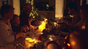 Extended family having Christmas dinner. Extended family celebrating christmas together at home. Family of five sitting at dining table talking and having dinner stock video