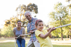 Extended family having tug of war. On a sunny day Stock Image