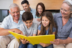 Extended family looking at album photo in living room Stock Photography