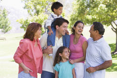 Extended family at the park smiling. Extended family standing in a park smiling Royalty Free Stock Images