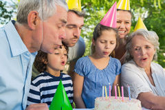 Extended family in party hats blowing birthday cake Royalty Free Stock Images