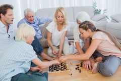 Extended family playing chess Stock Photography
