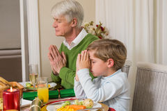 Extended family praying before christmas dinner Royalty Free Stock Images
