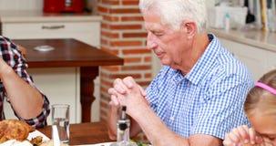 Extended family praying before dinner stock video