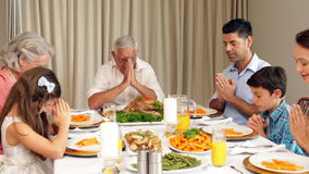 Extended family praying before dinner stock video footage