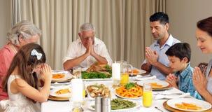Extended family praying before dinner Stock Photo