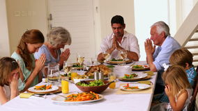 Extended family praying together before dinner stock video
