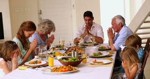 Extended family praying together before dinner Royalty Free Stock Photography