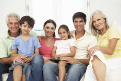 Extended Family Relaxing On Sofa At Home Together Stock Photo