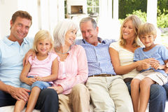 Extended Family Relaxing Together On Sofa Stock Photo