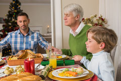 Extended family saying grace before christmas dinne. R at home in the living room Royalty Free Stock Photography
