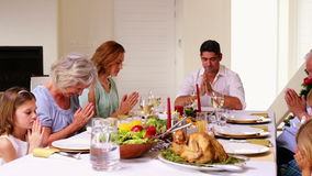 Extended family saying grace before christmas dinner Stock Photos