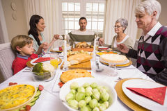 Extended family saying grace before christmas dinner. At home in the living room Stock Photo