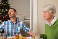 Extended family saying grace before christmas dinner Royalty Free Stock Photos