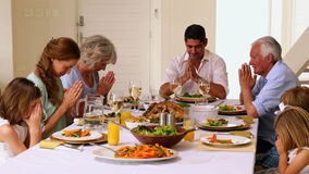 Extended family saying grace together before dinner stock video
