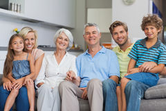 Extended family sitting on couch in living room Stock Photos