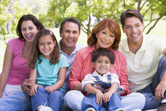 Extended family sitting outdoors smiling. Extended family sitting down in the park Royalty Free Stock Photos