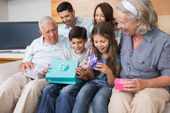 Extended family sitting on sofa with gift boxes in living room Royalty Free Stock Images