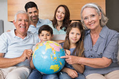 Extended family sitting on sofa with globe in living room Stock Photo