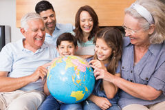 Extended family sitting on sofa with globe in the living room Royalty Free Stock Photos