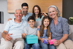 Extended family on sofa with gift boxes in living room Stock Photos