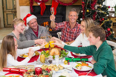 Extended family toasting at christmas dinner Royalty Free Stock Photos