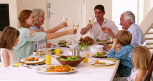 Extended family toasting at dinner Stock Image