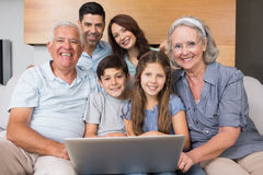 Extended family using laptop on sofa in living room Stock Photography