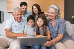 Extended family using laptop on sofa in living room Stock Images