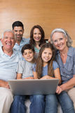 Extended family using laptop on sofa in living room Royalty Free Stock Photo