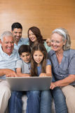 Extended family using laptop on sofa in living room Royalty Free Stock Photography