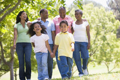 Extended family walking in park holding hands. And smiling Royalty Free Stock Photography