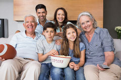 Extended family watching tv on sofa in the living room Stock Photos