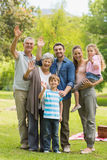 Extended family waving hands in park Royalty Free Stock Image